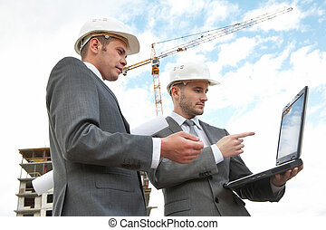 Working with laptop - Portrait of two builders standing at...