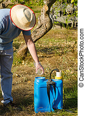 Working with pesticide - Agricultural worker filling a ...
