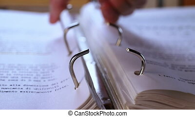 Adding page in ring binder, closing clip ,hands writing notes on page with pink pen , macro lens