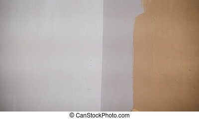 working with roller Hand paints the wall in orange color.