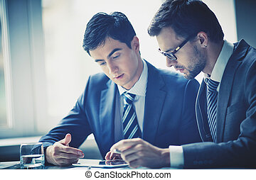 Working with touchpad - Image of two young businessmen using...