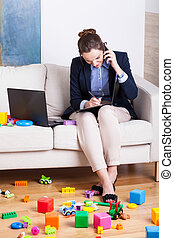 Working woman among child's toys - Working woman talking on...