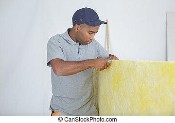 Workman cutting insulation