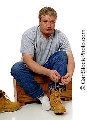 Workman Dressing - A man dressing for his construction job,...