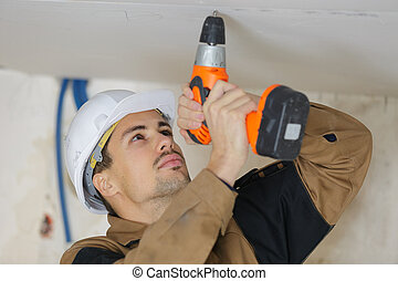 Workman drilling into ceiling