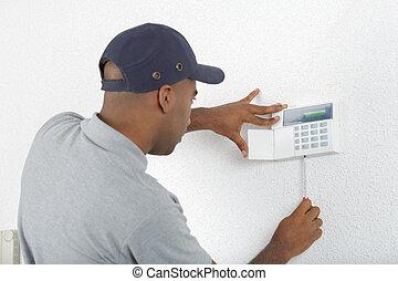 Workman fitting alarm key pad to wall