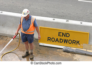 Workman hosing, roadwork signage.