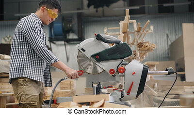 Workman in protective goggles is using air compressor to blow sawdust from circular saw working in workshop, dust is flying around. People and factory concept.
