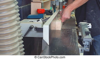 Workman in joinery workshop. - Man using drill press to...