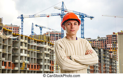 Workman in red helmet on background of buildings under...