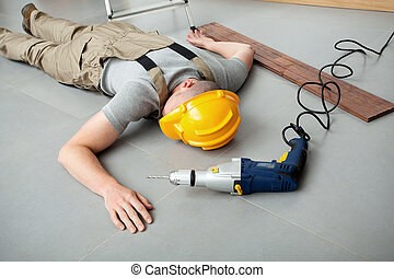 Workman injured at work - Workman lying on the floor and...