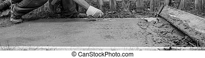 Workman leveling the surface of a concrete plate