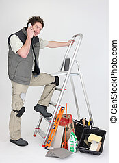 workman making a call near ladder and miscellaneous tools