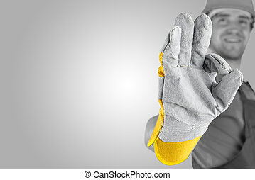Workman making a perfect gesture with his gloved hand with ...