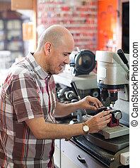 Smiling mature worker making duplicates of keys on laser machine.