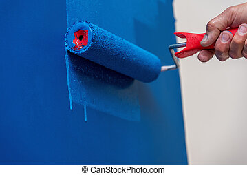 workman painting the wall in blue