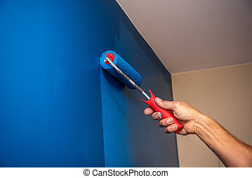 workman painting the wall in blue.