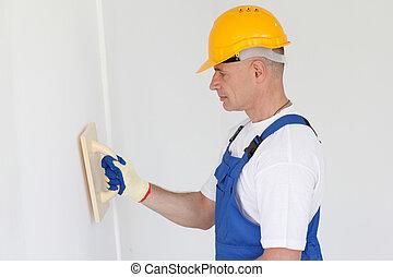 Workman polishing wall
