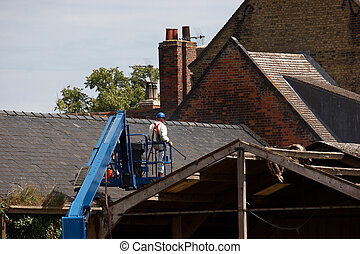 Workman removing roof of a derelict building