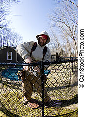 workman repairing building chain link fence - workman...