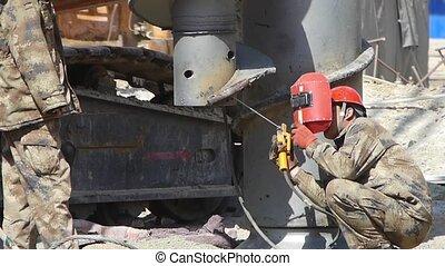 workman welding Heavy Machinery in Construction site.80:...