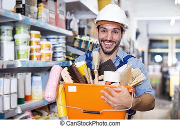Workman with tools in hands satisfied in shop