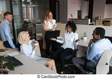 Workmates take a break during workday drinking coffee and chatting