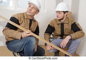 workmen crouching looking at floorboard
