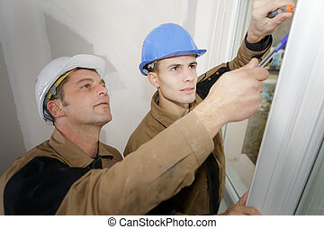 Workmen fitting new window