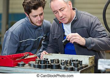 workmen looking through socket set