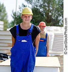 Workmen on a building site - Two young workmen carrying an...