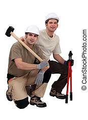 Workmen with sledgehammer and bolt cutters
