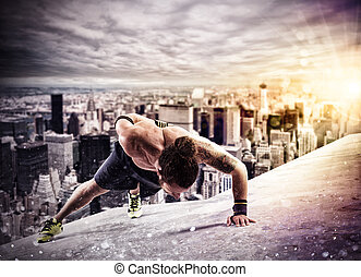 Workout above the roof of a building in the city - Muscular...