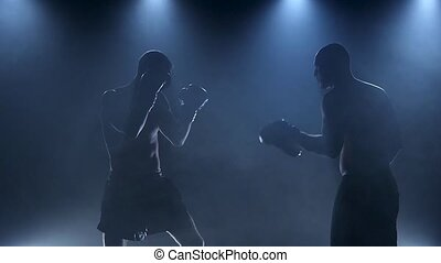 Workout blows in sparring of two boxers. Silhouette in smoke...