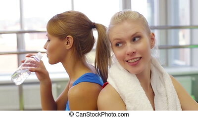 Workout break - Charming young women taking a workout break...