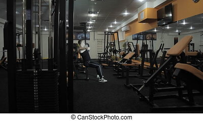 Workout in the gym - Man makes exercises on the simulator in...