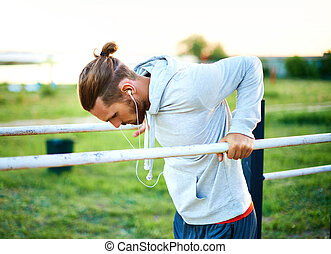 Workout outside - Young man training on sport equipment...