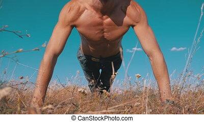 Workout. Pushups Fitness Man doing Push-ups Outside on...