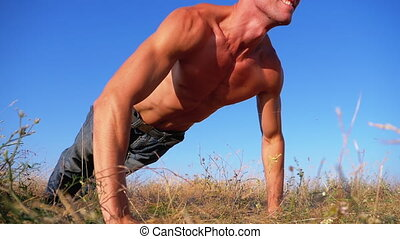 Workout. Strong Man doing Push-ups with Claps Outside on...