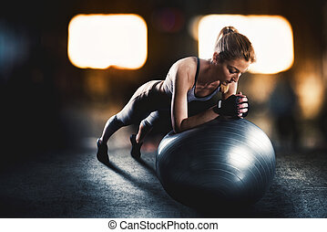 Workout with fitness ball - Muscular woman on a fitness ball...
