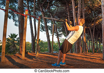 workout with suspension straps in a park