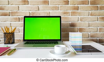 Workplace of a businessman. Laptop with green screen on a table,