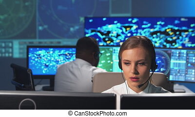 Workplace of the air traffic controllers in the control tower. Diverse team of professional aircraft control officers works using radar, computer navigation and digital maps. Aviation concept.