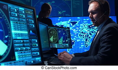 Workplace of the air traffic controllers in the control tower. Team of professional aircraft control officers works using radar, computer navigation and digital maps. Aviation concept.