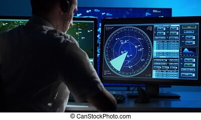 Workplace of the professional air traffic controller in the control tower. Caucasian aircraft control officer works using radar, computer navigation and digital maps. Aviation concept.