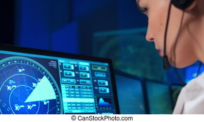 Workplace of the professional air traffic controller in the control tower. Caucasian female aircraft control officer works using radar, computer navigation and digital maps. Aviation concept.