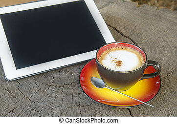 workplace, office desk: cap of coffee and tablet pc