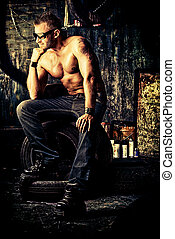 workplace - Handsome muscular man in the old garage.