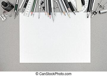 workplace with blank sheet of paper and various drawing tools
