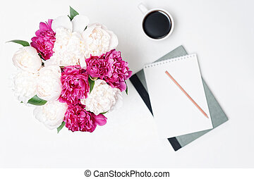 Workplace with cup coffee paper pen pink white peony flowers